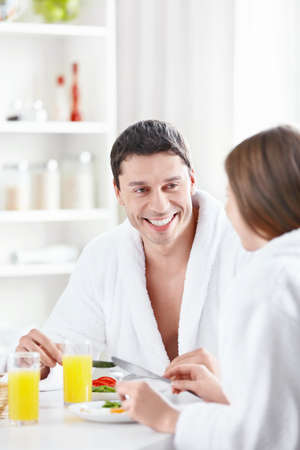 Attractive young couple eating breakfast in the kitchen photo
