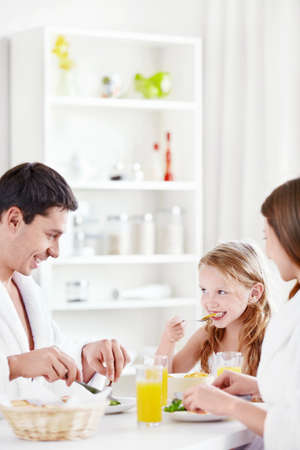 A happy family with a child eating breakfast in the kitchen photo