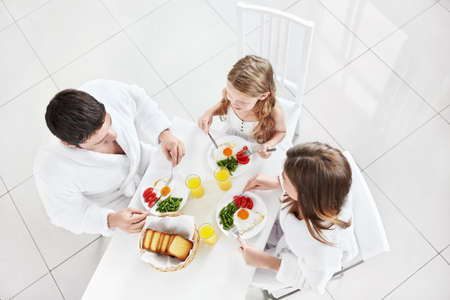 Family with a child eating breakfast in the kitchen photo