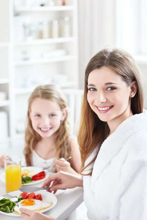 A mother and child have breakfast in the kitchen photo