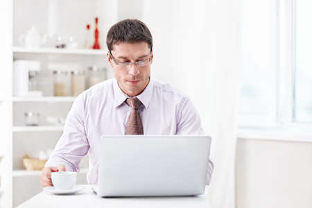 A man with a laptop and a cup in the kitchen photo