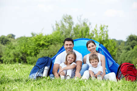 campsite: A happy family with a tent outdoors
