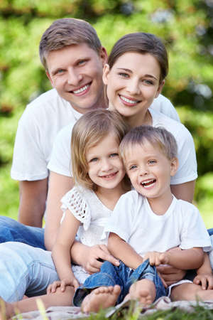 family on grass: A happy family with kids in the park Stock Photo