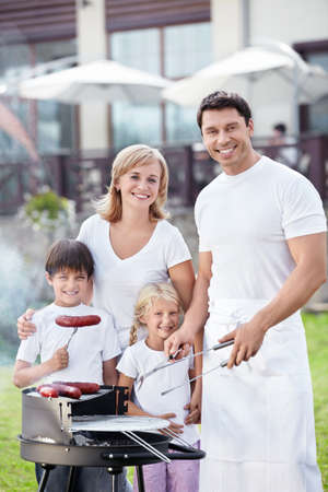 Families with children with barbecue outdoors photo
