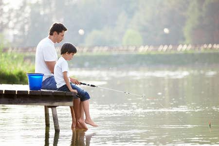 hombre pescando: Hombre y ni�o de pesca en el lago Foto de archivo