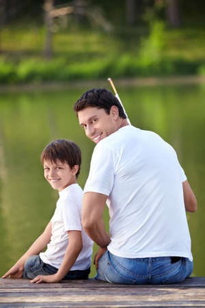 A man and a boy with a fishing rod on the lake photo