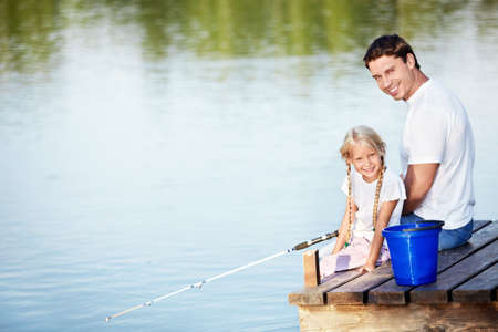 Father and daughter go fishing on the lake photo