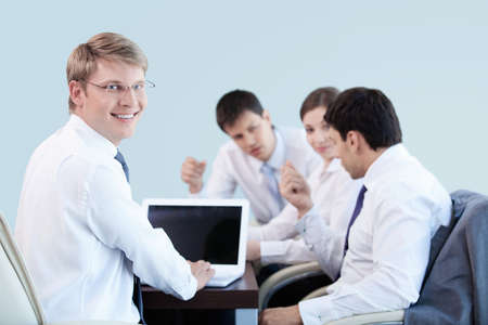 Young businessman with laptop in office photo