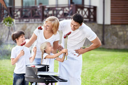 white sausage: Parents with children at barbecue