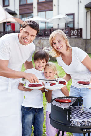 Happy family with barbecue outdoors photo