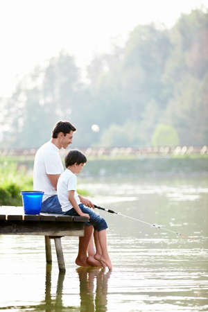 Father and son fishing on the lake photo