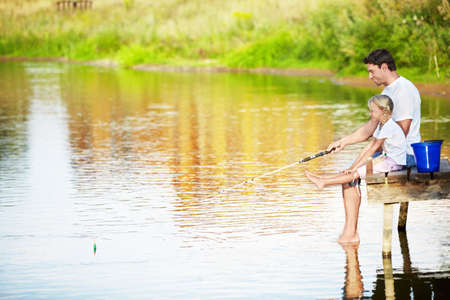 dad and daughter: Father and daughter fishing on the lake Stock Photo