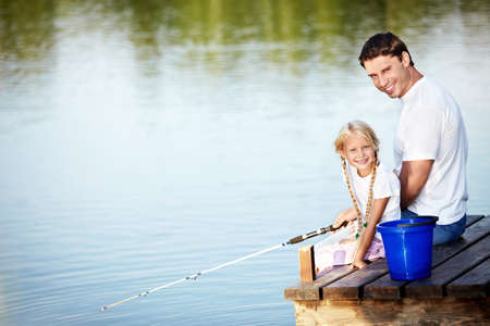 children pond: Father and daughter fishing on the lake Stock Photo