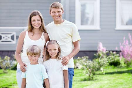 familia en jardin: Una familia feliz alrededor de la casa