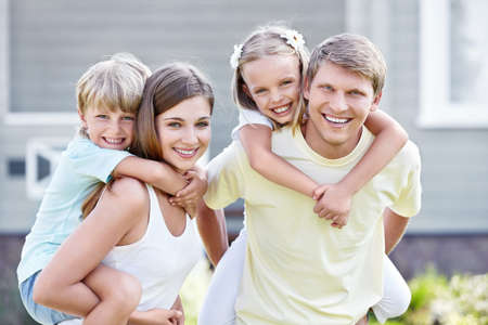 front of house: Smiling family with children outdoors
