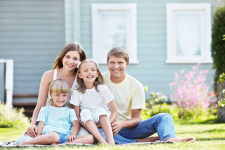 front of house: Laughing family with children outdoors Stock Photo