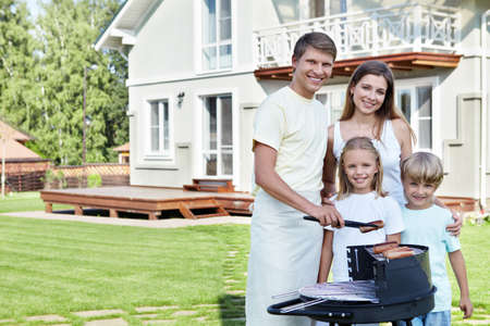 fachada de casa: Familias con ni�os contra la casa con una barbacoa Foto de archivo