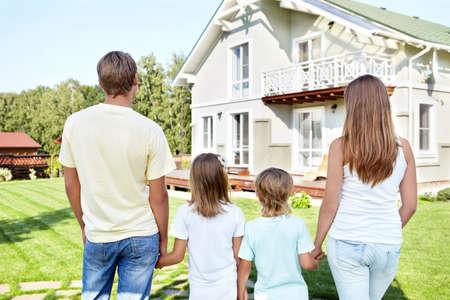 fachada de casa: Familia con ni�os mirando la casa