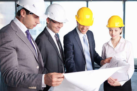 Business people in hard hats at construction site Stock Photo