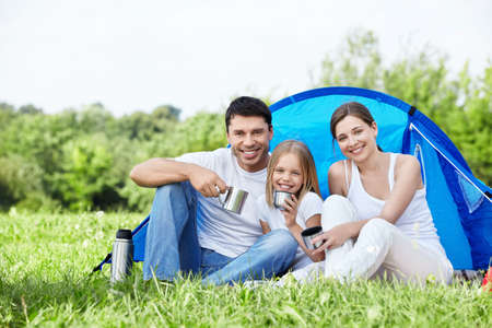 Family with a child in a tent on the nature photo