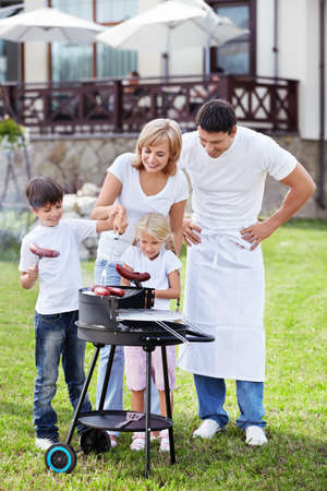 family picnic: Happy family with barbecue outdoors