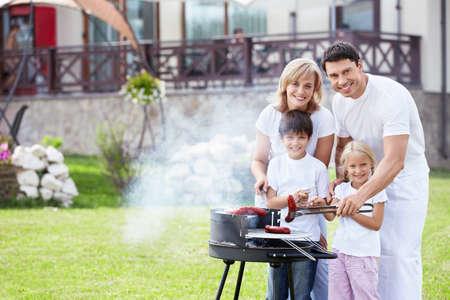 family picnic: Familia feliz con barbacoa al aire libre