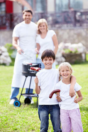Happy family with children make barbecue photo