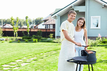 home garden: A couple with a barbecue on the lawn