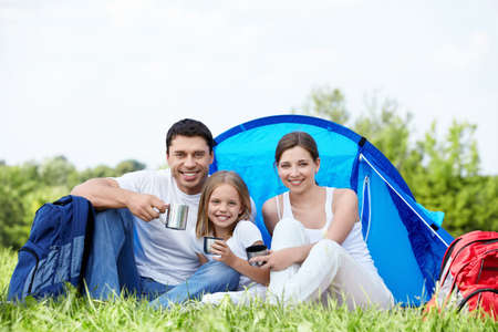 A young family with a tent on the nature photo