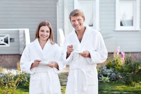 dressing gowns: Young couple in dressing gowns with cups Stock Photo