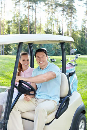 Smiling couple in the car for golf photo