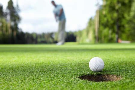 balle de golf: Golfeur conduit la balle dans le trou