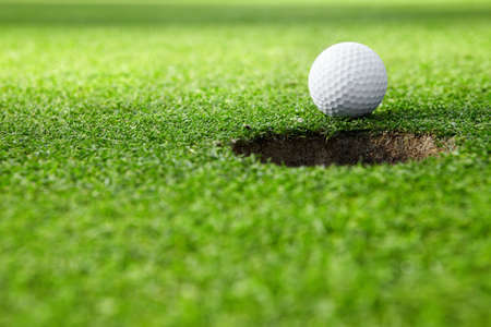 Une balle de golf dans le trou Banque d'images