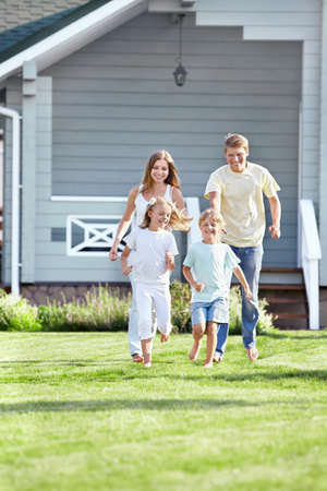 front house: Running a family on the lawn Stock Photo
