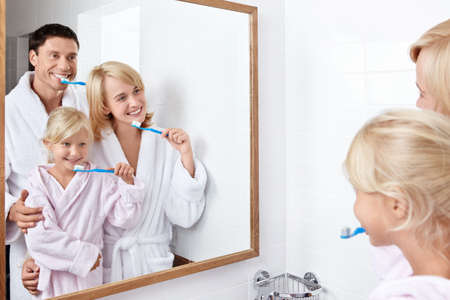 bathroom mirror: Family brushing their teeth in the bathroom