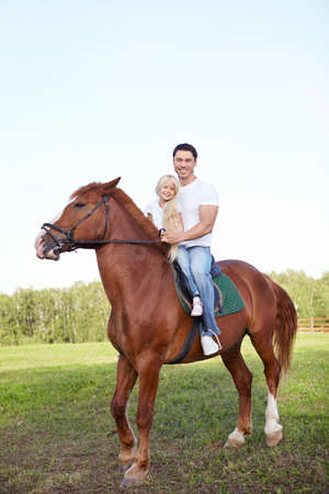 Little girl with her father on a horse photo
