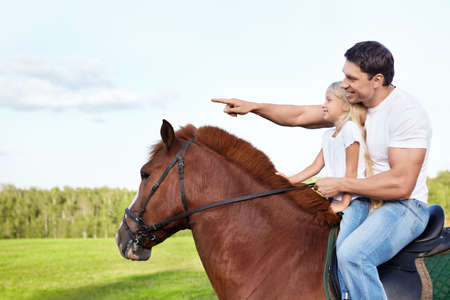 Father and daughter on a horse photo