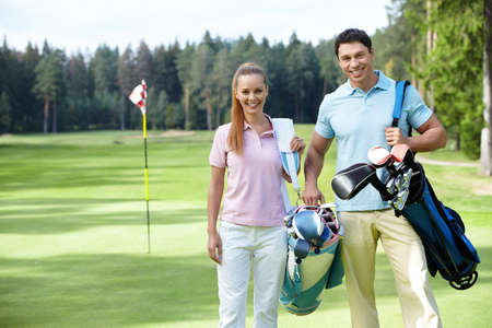 golfers: Young couple on the golf course