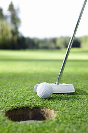 putter: Ball and golf club in the hole