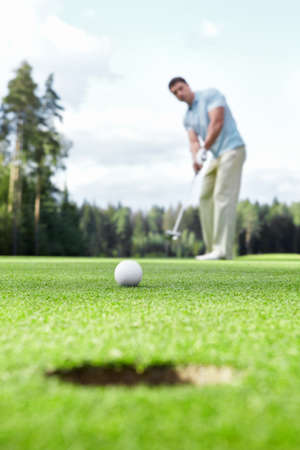golf green: Man plays golf on the golf course Stock Photo