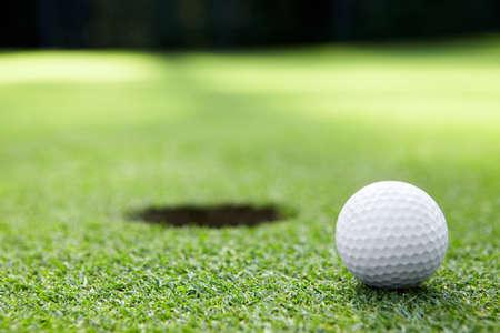 De bal bij de hole op de golfbaan Stockfoto