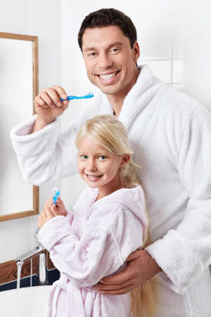 Father and daughter brushing their teeth in the bathroom photo