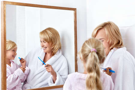 Mother and daughter brushing their teeth in the bathroom Stock Photo - 11420278