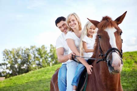 femme a cheval: Famille sur un cheval