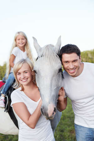 Parents and child with a horse photo