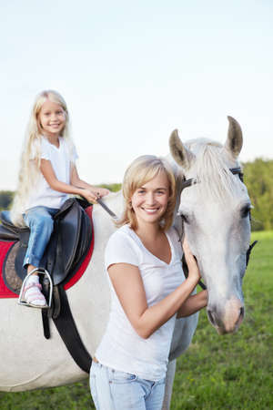 horse harness: Mother and daughter with a horse Stock Photo