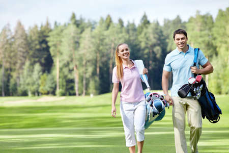 play golf: Young couple with clubs on the golf course