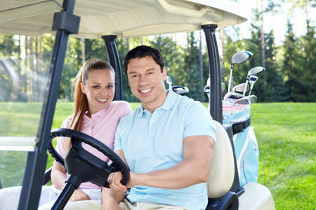 golf cart: Young couple in a golf car