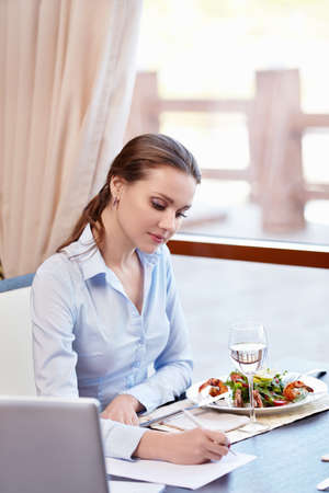 Woman signs a document in a restaurant