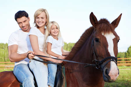 riding horse: Attractive family on a brown horse Stock Photo